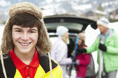 подросток, улыбаясь в камеру во время семейной нагрузки лыжи в багажнике — Стоковое фото