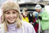 мать улыбаясь в камеру, хотя семьи нагрузки лыжи в багажнике автомобиля — Стоковое фото