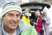 отец, улыбаясь в камеру в то время как семьи нагрузки лыжи в багажнике автомобиля — Стоковое фото