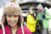 девочка-подросток, улыбаясь в камеру во время семейной нагрузки лыжи в boot o — Стоковое фото