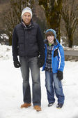 Father And Son Walking Along Snowy Street In Ski Resort — Stock Photo