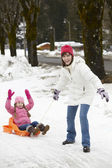 Mother Pulling Daughter On Sledge Along Snowy Street In Ski Reso — Stock Photo