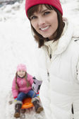Mother Pulling Daughter On Sledge Along Snowy Street In Ski Reso — Stockfoto