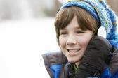 Chlapec sluchátka a poslech hudby na sobě zimní clo — Stock fotografie