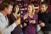 Grupo de amigos disfrutando de beber juntos en barra — Foto de Stock