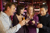 Group Of Friends Enjoying Drink Together In Bar — Stock Photo