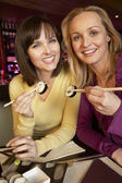 Two Women Enjoying Sushi In Restaurant — Stock Photo