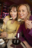 Two Women Enjoying Sushi In Restaurant — Stock Photo