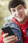 Teenage Boy Texting On Smartphone Wearing Winter Clothes — Stock Photo