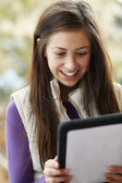 Teenage Girl Using Tablet Computer Outdoors Wearing Winter Cloth — Stock Photo