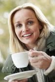 Woman In Outdoor Café With Hot Drink Wearing Winter Clothes — Stock Photo
