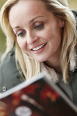Outdoor Portrait Of Woman Wearing Winter Clothes Reading Magazin — Stock Photo