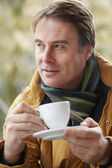 Man In Outdoor Café With Hot Drink Wearing Winter Clothes — Stock Photo
