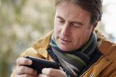 Sms uomo su smartphone indossando abiti invernali — Foto Stock