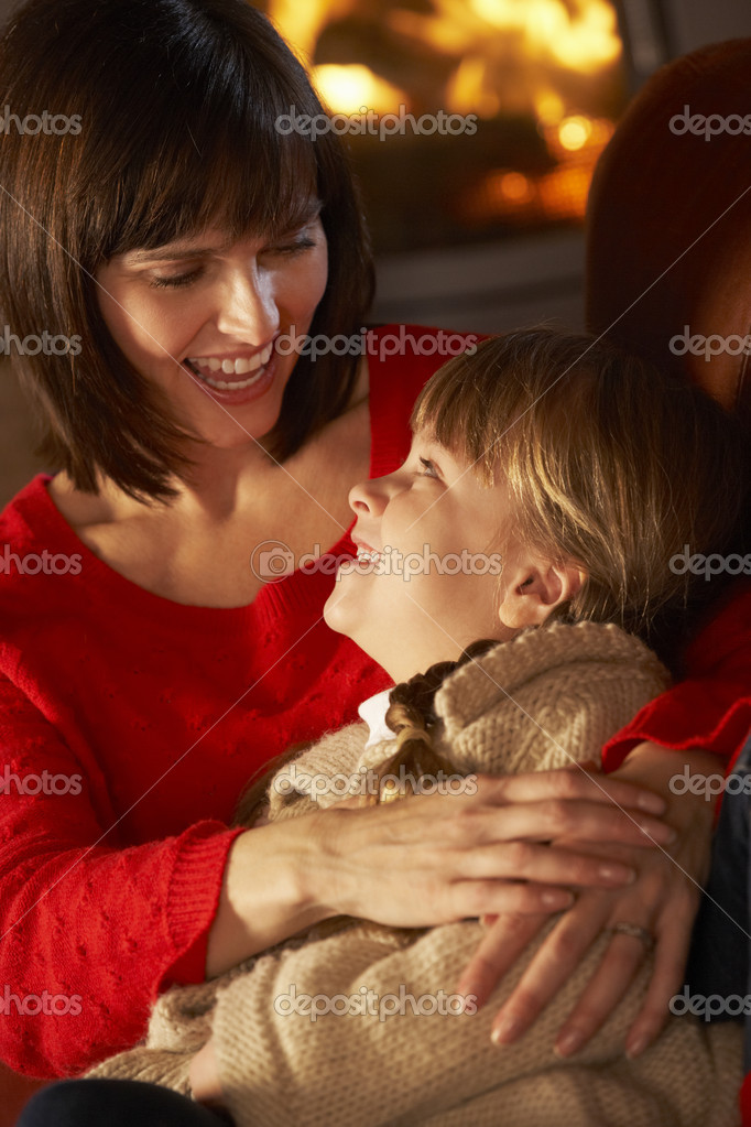 Mother And Daughter Relaxing On Sofa By Cosy Log Fire — Stock Photo #11890776