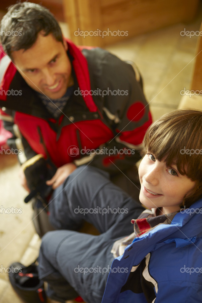 Father Helping Son To Put On Warm Outdoor Clothes And Boots — Stock Photo #11891127