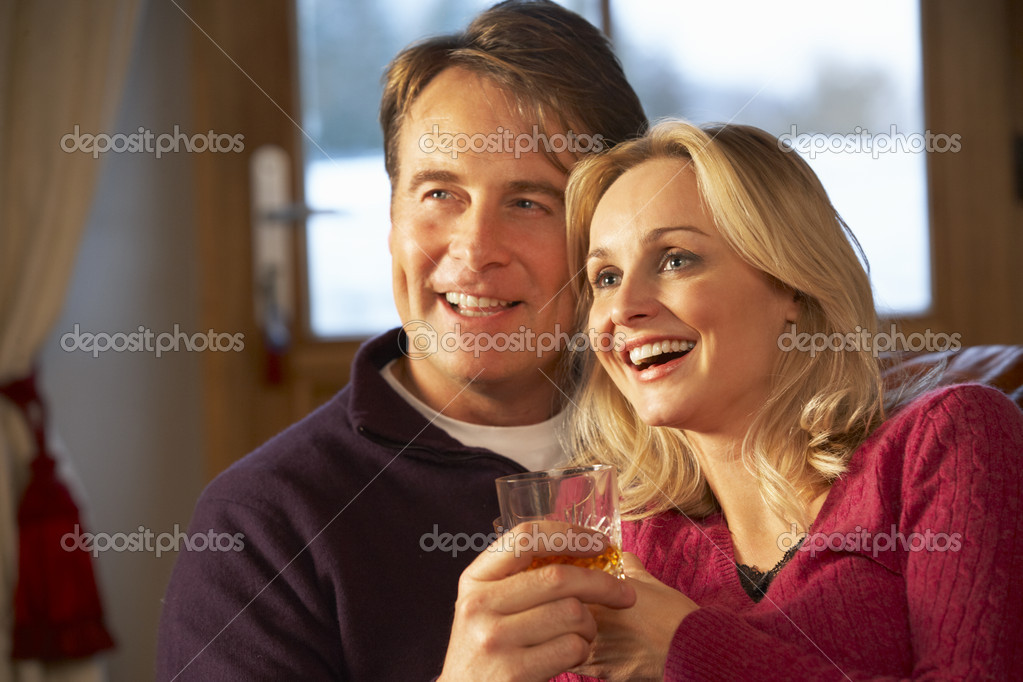 Middle Aged Couple Sitting On Sofa With Glasses Of Whisky Watching TV  Stock Photo #11891315