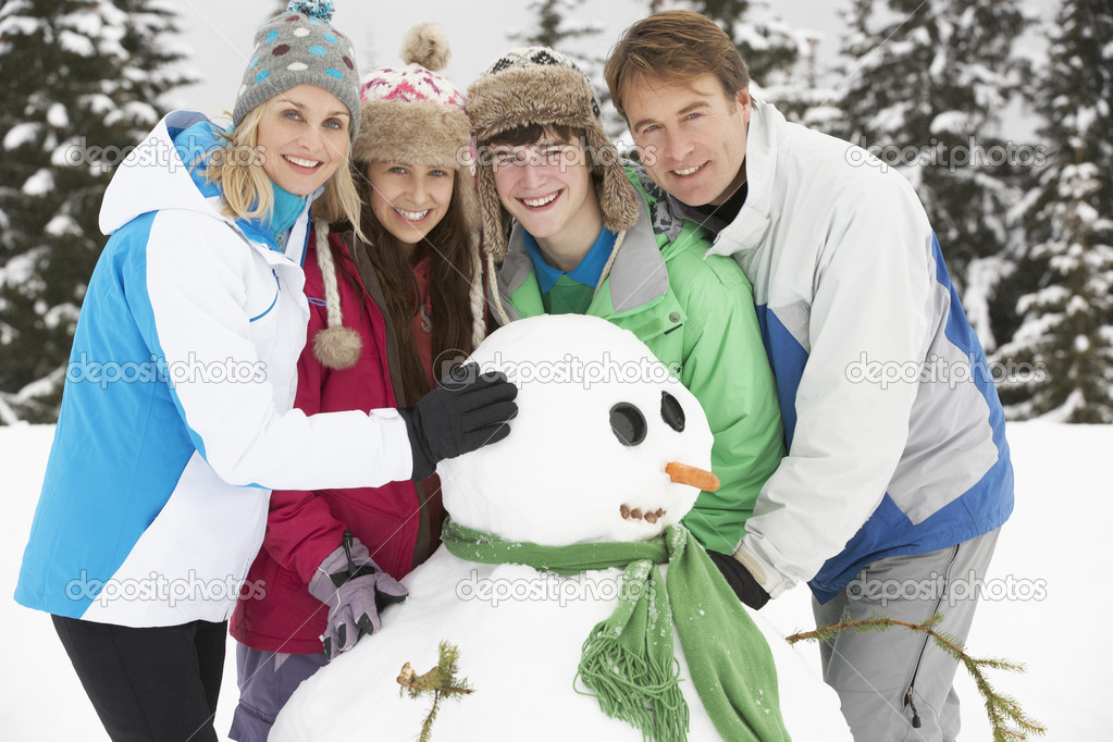Teenage Family Building Snowman On Ski Holiday In Mountains — Stok fotoğraf #11891965
