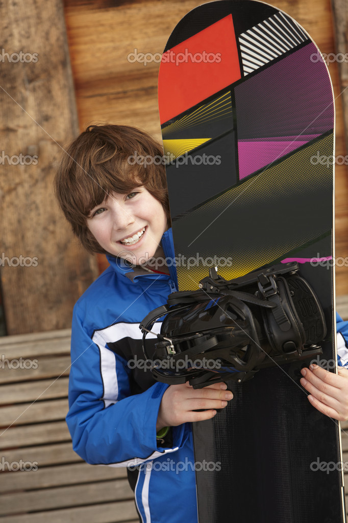 Boy With Snowboard On Ski Holiday In Front Of Wooden Background — Stock Photo #11892367