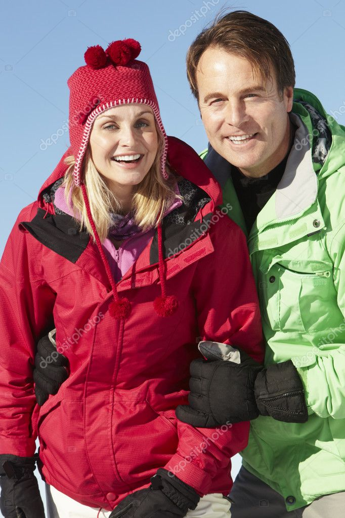 Couple Standing In Snow Wearing Warm Clothes On Ski Holiday In Mountains — Stock Photo #11892906