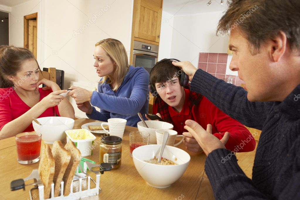 Parents Taking Away Gadgets From Children Whilst Eating Breakfast Together In Kitchen — Stock Photo #11893375