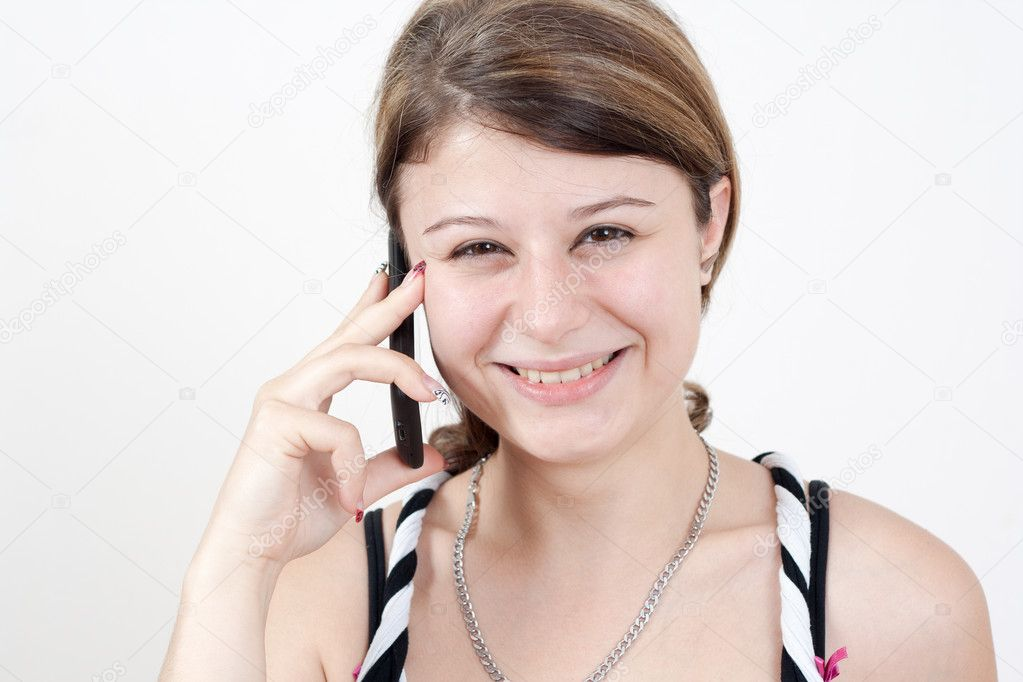Young smiling brunette girl is talking to someone over her smartphone. all on white background — Stock Photo #12103004