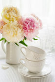 White cups and a bouquet of peonies — Stock Photo
