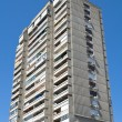 Tall concrete apartment building over blue sky — Stock Photo