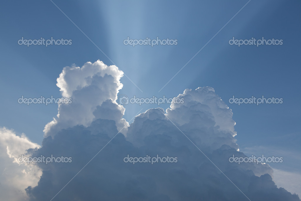 Bright sun behind clouds lightstreaks in the blue sky  Stock Photo #10852374