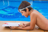 Boy reading near pool — Stock Photo