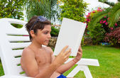 Boy reading on summer lawn — Stock Photo
