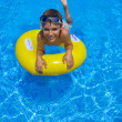 Boy swimming on rubber ring in pool — Stock Photo #11416898