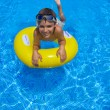 Boy swimming on rubber ring in pool — Stock Photo