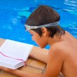 Stock Photo: Kid reading near pool