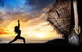 Yoga silhouette warrior pose near boat — Stock Photo