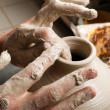 Stock Photo: Hands of potter, creating earthen jar on circle