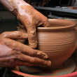 Royalty-Free Stock Photo: Hands of a potter, creating an earthen jar on the circle