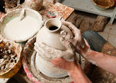 Potter creating earthen jar on the circle — Stock Photo