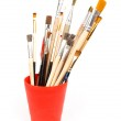 Paint brushes in red glass — Stock Photo #11800640
