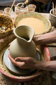 Hands of a potter, creating an earthen jar of white clay — Stock Photo