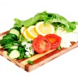 Fresh fruits and vegetables on a bamboo cutting board - Stock Photo
