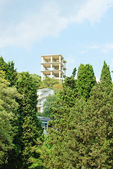 New apartments building over blue sky and green tree.Crimea. Ukraine. — Stock Photo