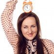 Young woman holding a clock on her head — Stockfoto
