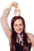 молодая женщина, держащая часы на голове — Стоковое фото