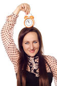 Mladá žena drží hodiny na hlavu — Stock fotografie