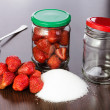 Strawberry cleared on a table with a hill of sugar and empty jars with covers for house conservation — Stock Photo