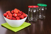 Strawberry cleared in a white bowl and empty jars with covers for house conservation — Stock Photo