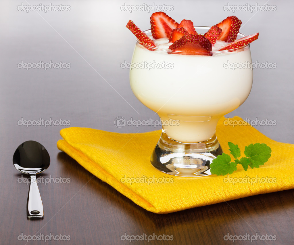 Yogurt with strawberry slices in a kremanka on a yellow napkin with a spoon, located on a brown table with a wood structure — Stock Photo #11379820