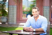 Smiling man seated at a table — Stock Photo