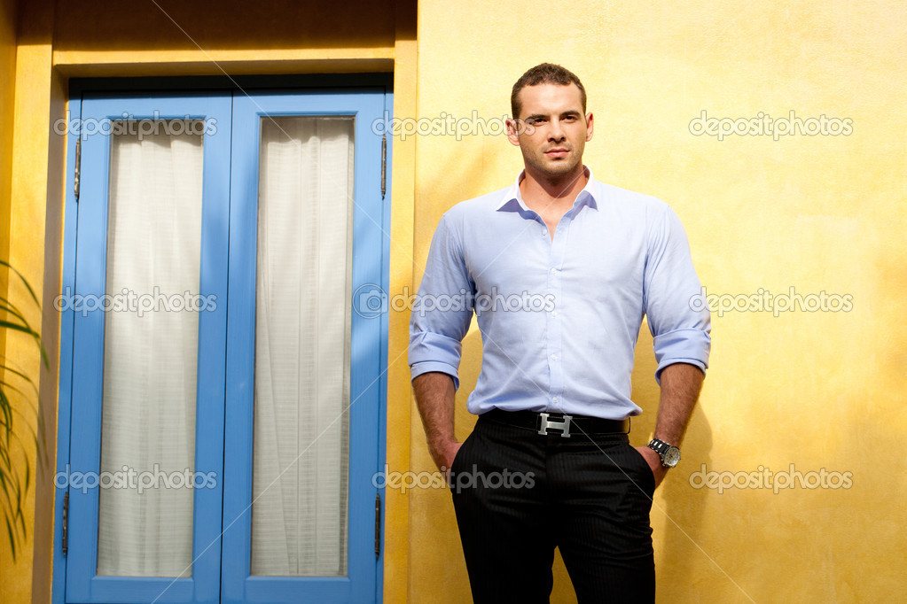 Young adult man standing next to yellow wall — Stock Photo #11083727